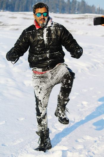 Portrait of young man gesturing while standing on snow covered field