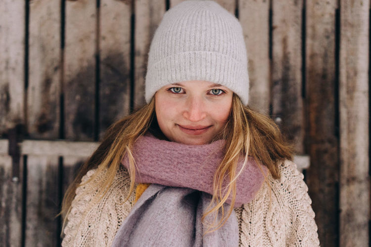 Portrait of woman wearing hat against fence during winter