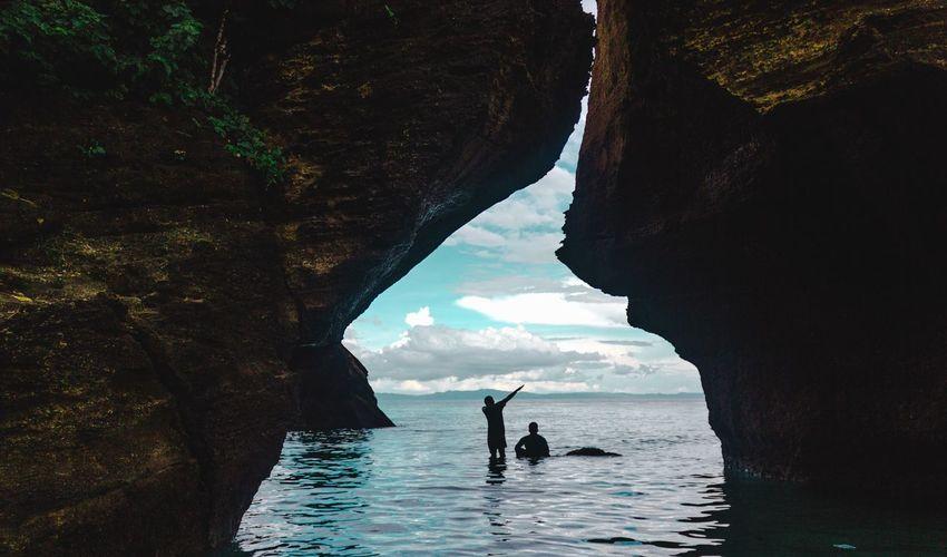 Silhouette people swimming in sea