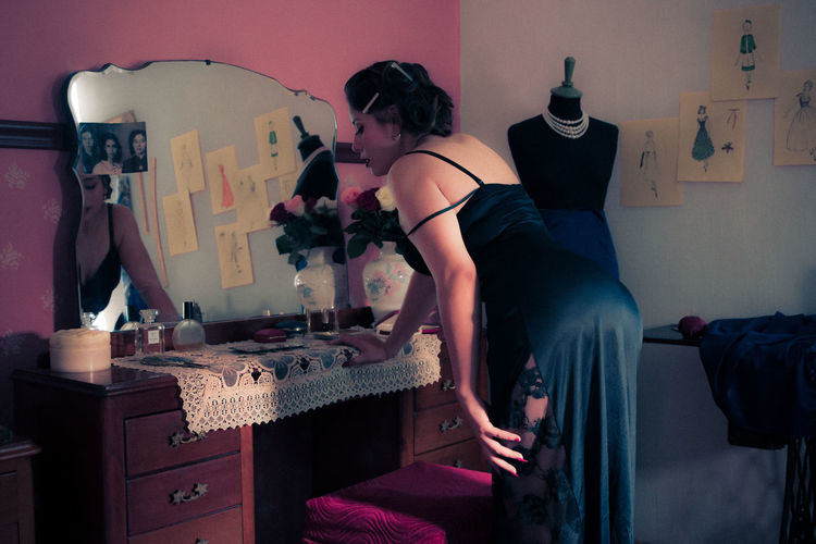Side view of woman wearing dress looking into mirror at studio