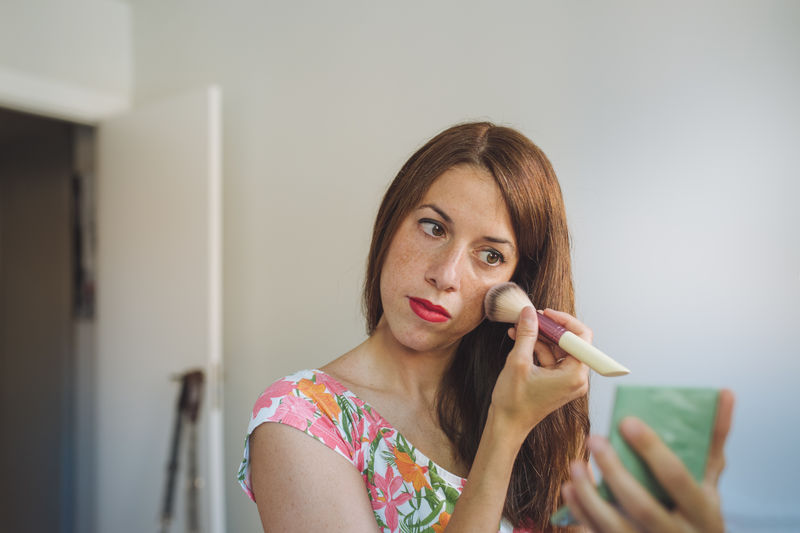 Portrait of young woman holding camera at home
