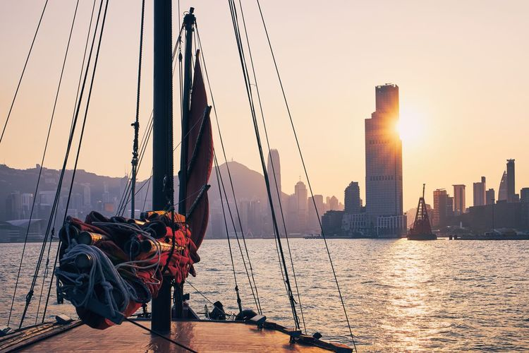 Sailboat in sea against cityscape during sunset