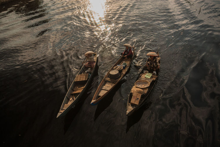 High angle view of people sitting in rowboats