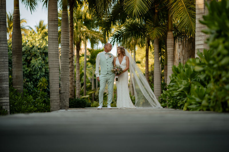 Couple walking on palm trees