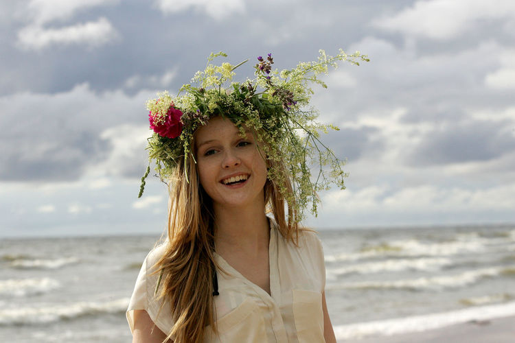 Portrait of smiling young woman by sea against sky