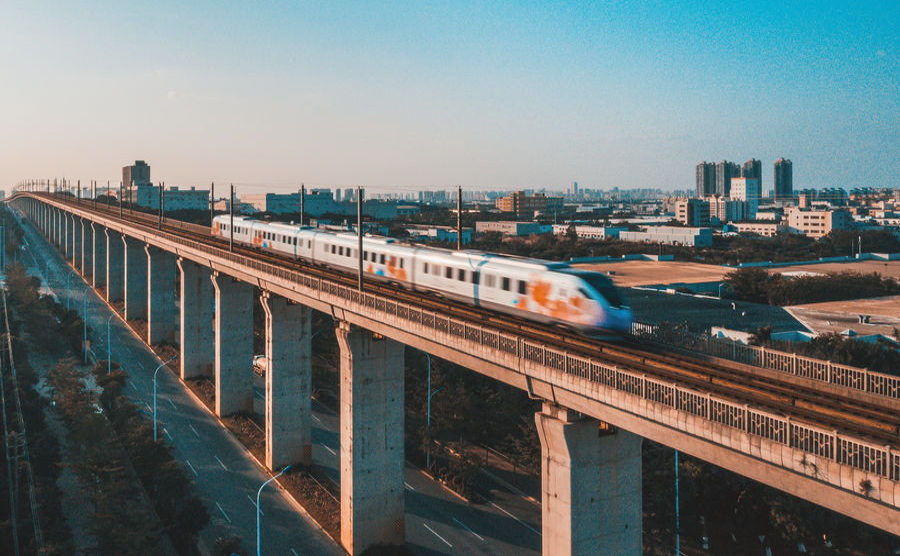 Train on bridge in city against clear sky