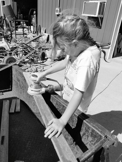 High angle view of girl sanding wood using sander in back yard