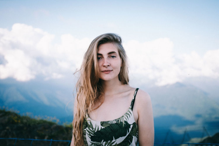 Portrait of smiling woman standing against mountains