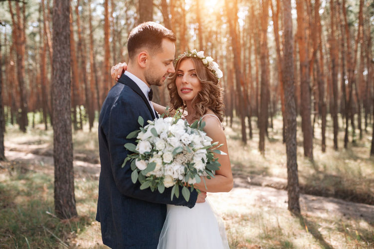 Newlywed Couple Standing In Forest