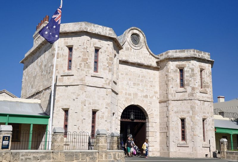 The limestone brick Fremantle Prison with Australian Flag in Fremantle, Western Australia. Arch Architecture Australian Flag Bell Tower - Tower Blue Brick Building Exterior Clear Sky Day Entrance Façade Flag Fremantle  Fremantle Prison In Front Of Leisure Activity Limestone Outdoors Person Prison Tourism Tourist Tourist Attraction  Visiting Western Australia