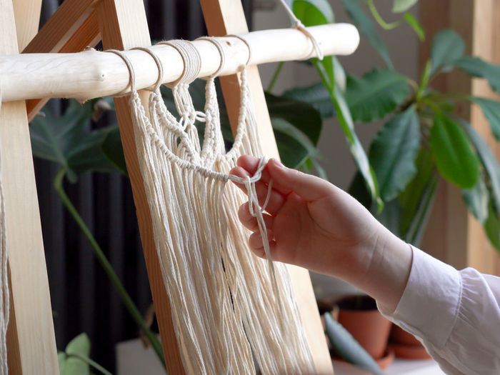 Close-up of woman hand touching thread on wood at home