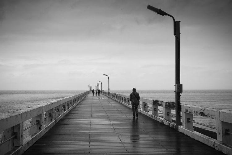 People walking on pier against sky