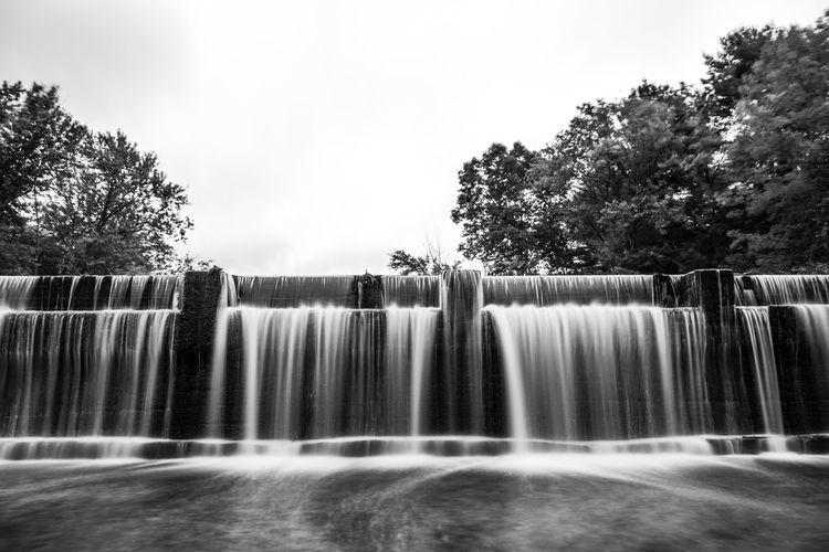 Water Splashing On Fountain Against Trees