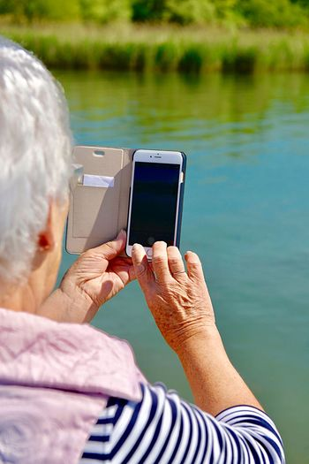 Rear view of senior woman photographing through smart phone at lakeshore