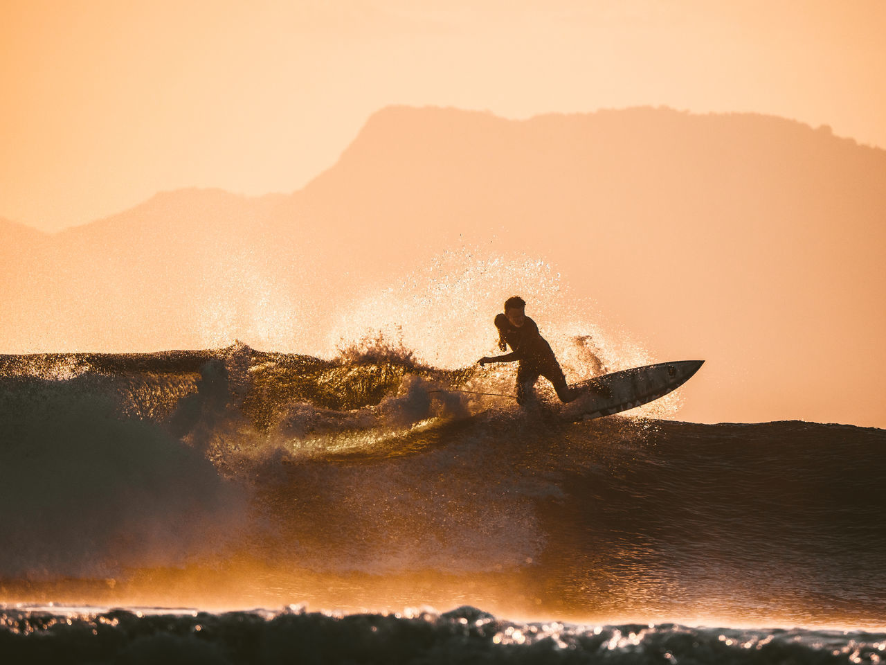 water, motion, sky, sport, real people, aquatic sport, sunset, nature, surfing, lifestyles, sea, one person, extreme sports, wave, splashing, adventure, beauty in nature, mountain, skill, outdoors, power in nature