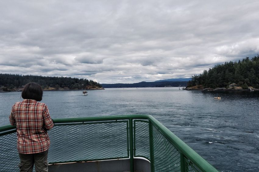 As we pull away from Friday Harbor. San Juan Islands Ferry Boat Travel Looking Into The Distance Person From The Back Woman Plaid Pacific Northwest  Sea Cloudy Sky Water Boat Calm Reflecting Trees Shoreline On The Way People And Places My Year My View Long Goodbye Let's Go. Together.