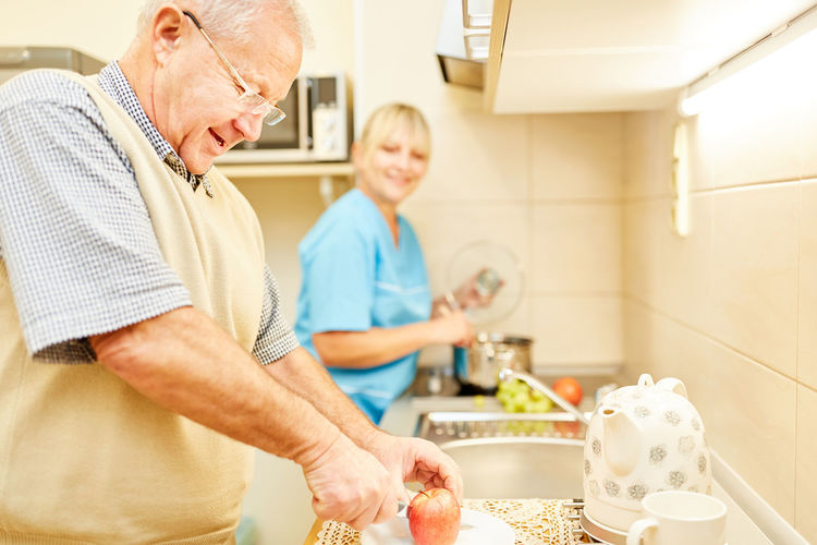 Man cutting apple with nurse preparing food in kitchen