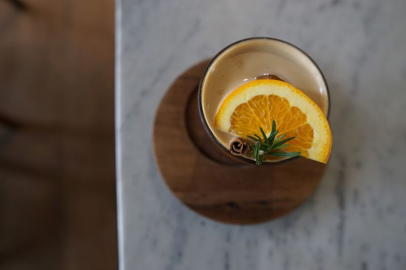 High angle view of orange with cinnamon and herb in cup on table