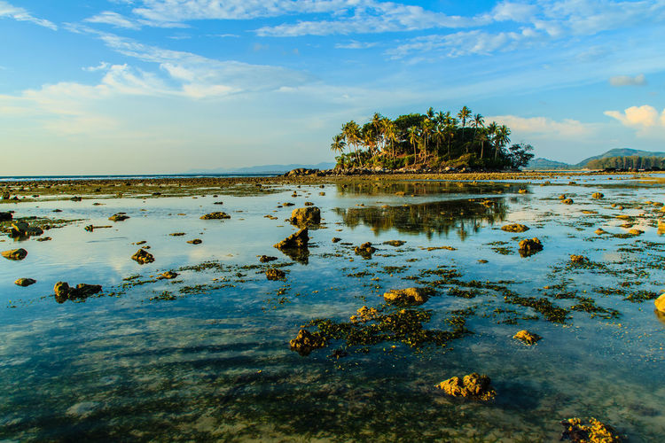 Lonely remote island with rock beach. Beautiful rocky coastline with full of stones on the beach when the sea water receded with dramatic blue sky background on the cloudy day. Coastline Coastline Landscape Coastline Nature Water Lonely Lonely Island Lonely Place  Peaceful View Rock Beach Sea Rocky Beach Rocky Coastline Rocky Shore Beauty In Nature Cloud - Sky Coastline Sky Day Lake Lonelyplanet Nature No People Outdoors Peaceful Peaceful Nature Peaceful Place Reflection Rock Beach Rocky Coast Rocky Landscape Scenics Sky Tranquil Scene Tranquility Tree Water