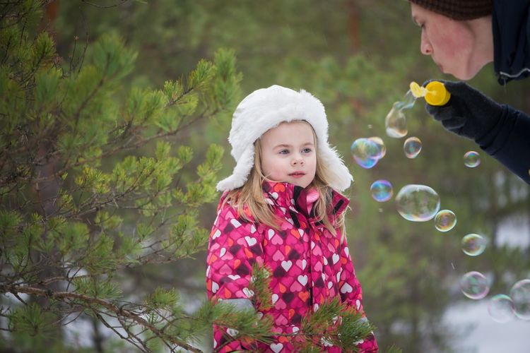 Daughter Looking At Mother Blowing Bubbles