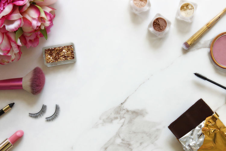 High angle view of beauty products with chocolate bar on table