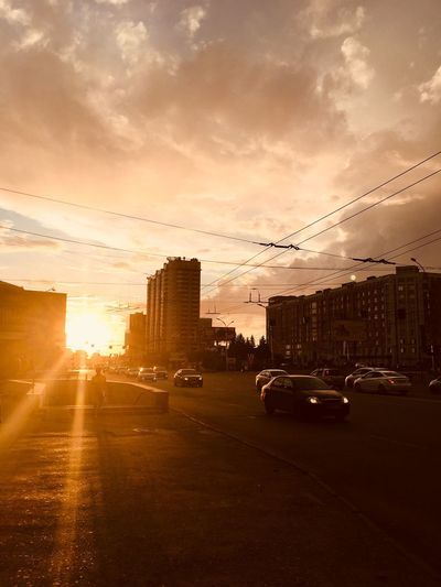 Cars on street by buildings against sky during sunset