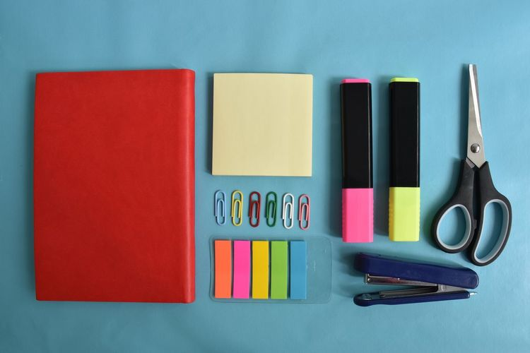Variation Multi Colored Choice Indoors  Directly Above Pen No People Still Life Scissors Table Arrangement Studio Shot Large Group Of Objects Office Supply Group Of Objects In A Row Note Pad Watercolor Paints Blue Background Postit Red Stapler