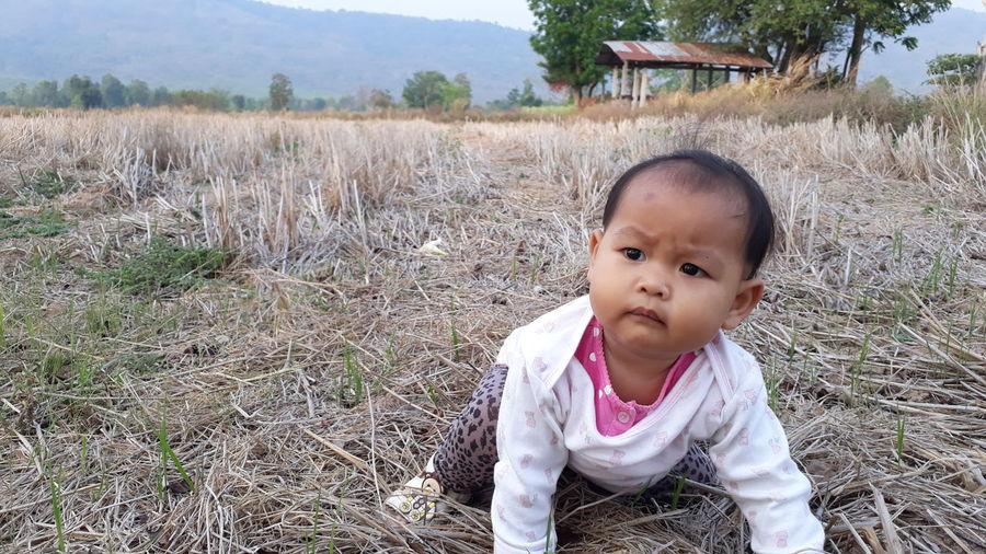 Cute Baby Girl Crawling On Field