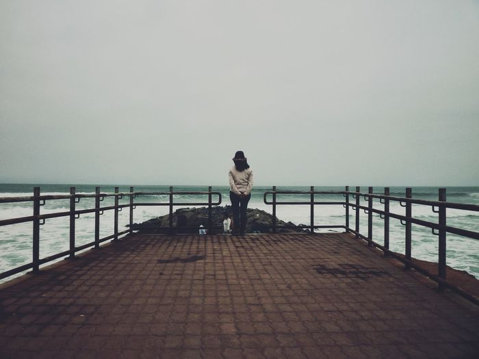 Rear view of woman standing on pier by sea against sky