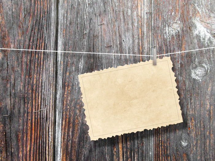 Close-Up Of Paper Hanging On String Against Wooden Wall