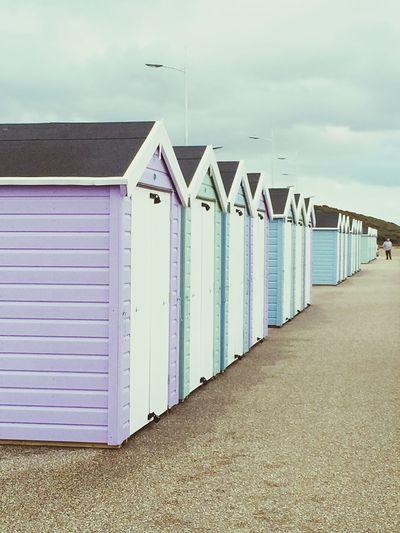 Row Of Beach Huts Against Cloudy Sky