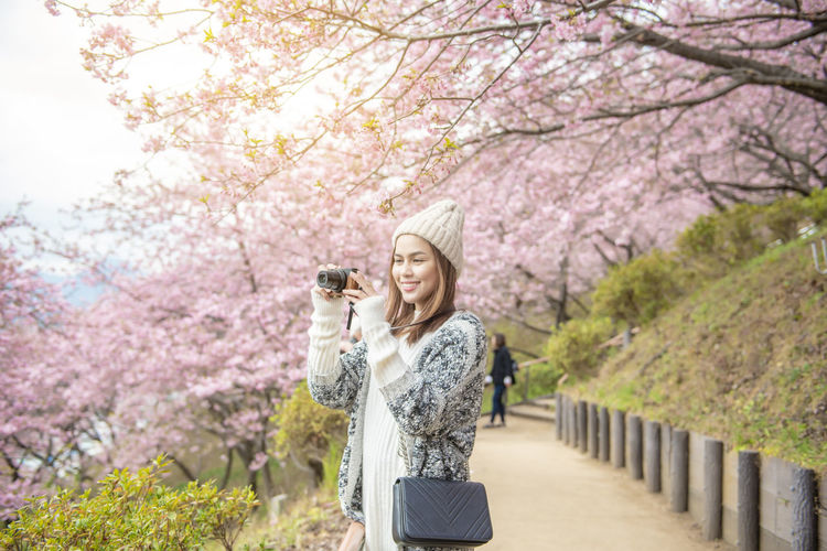 Woman holding camera while standing by cherry tree