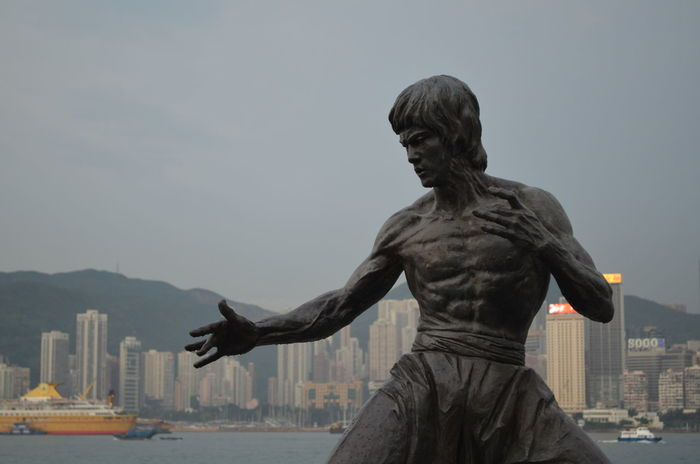 Bruce Lee After Rain Art And Craft Avenue Of Stars Bruce Lee Cityscape Focus On Background Hong Kong Human Representation Martial Arts Muscles No Edit/no Filter No Filter No People Portrait Rain Skycrapers Statue Strength Urban Envision The Future Embrace Urban Life