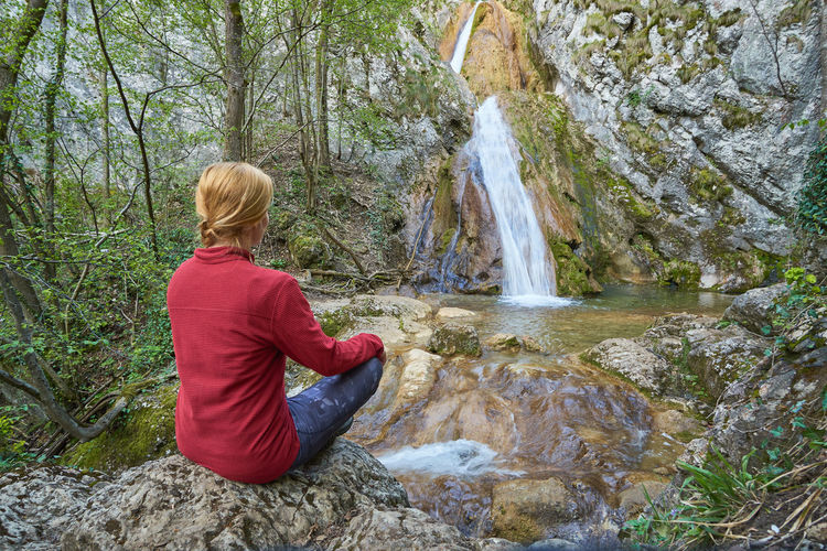 Man sitting on rock in forest