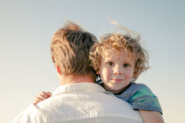 Adorable curly boy hugging dad. family concept. summer vacation in america nation parks background