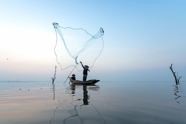 Fishermen throwing fishing net into sea against sky during sunset