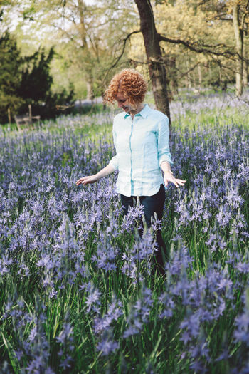 Happy woman standing amidst flowering plants against trees at forest