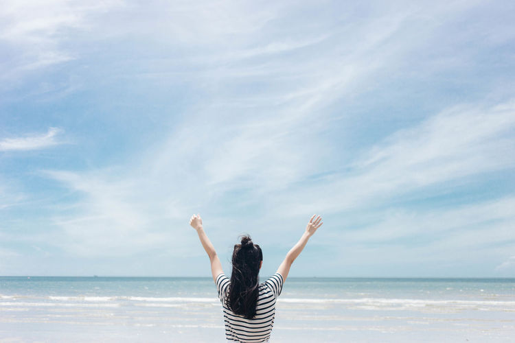 Rear view of woman with arms raised standing against sky at beach