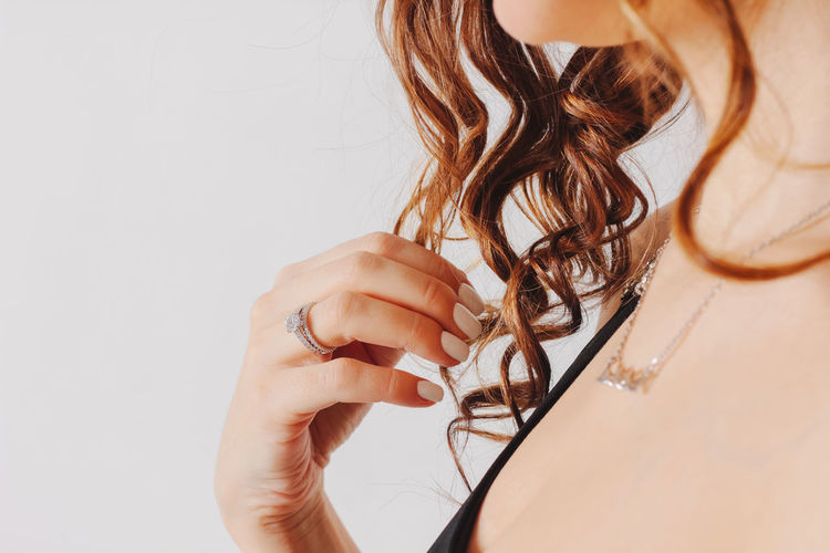 Close-up of woman holding hands over white background