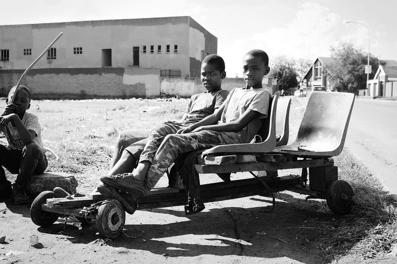 What Dreams may come - I grew up in Eldoradopark with all its social and economic problems, life was great. This picture reminds me of my childhood and the dreams I had at these guys ages. Just a clear message to never stop dreaming. Eldoradopark Johannesburg South Africa Black And White Backyard Bnw Urban Exploration Dreams The Street Photographer - 2018 EyeEm Awards Sitting Men Women Couple - Relationship Sky Settlement Urban Scene