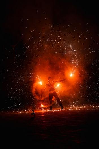 Silhouette people on illuminated fireworks at night