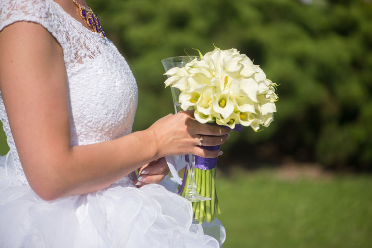 Midsection Of Bride Holding Bouquet On Field