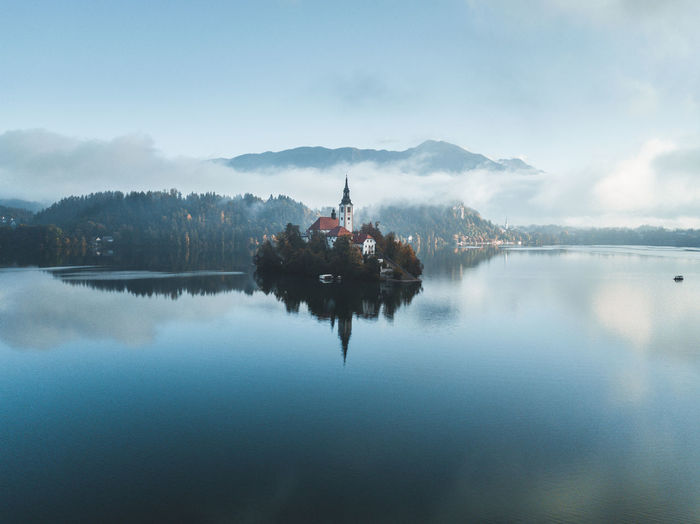 Scenic view of lake by building against sky. fantastic sunrise with mist in bled, slovenia