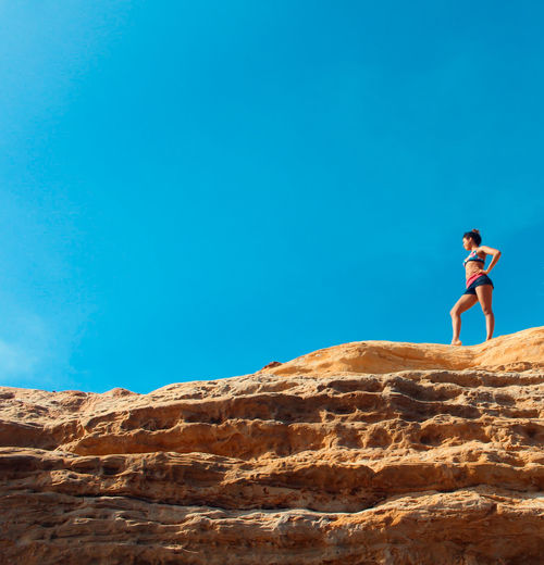 Low Angle View Of Young Woman In Bikini Standing On Rock Against Clear Blue Sky