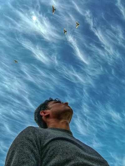 Low angle view of man looking up against blue sky