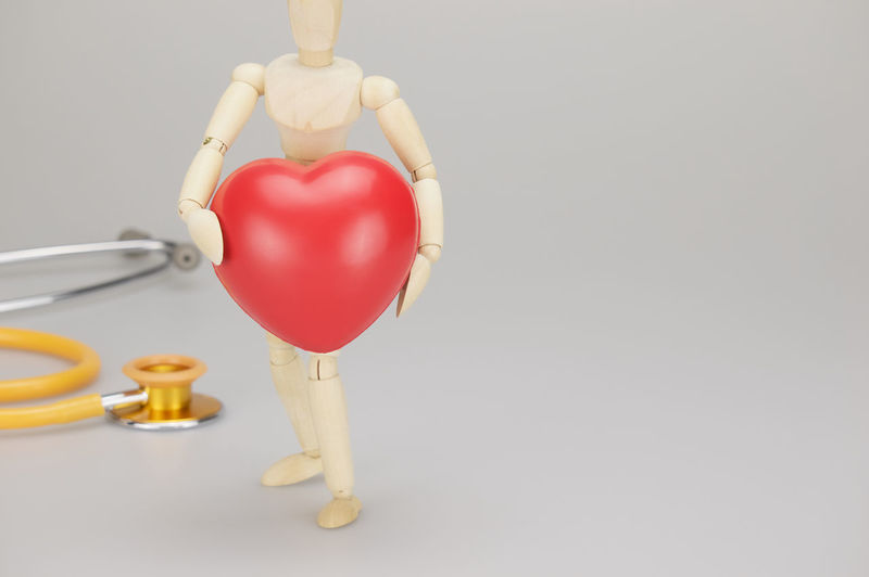 Wooden dummy holding red heart have blur yellow and gold stethoscope on white background. Care Curve Doctor  Gold Red Shape Therapy Wood Background Cardio Copy Space Dummy Equipment Health Heart Medical Stethoscope  Tool Treatment White Wooden