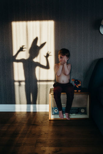 Portrait of shirtless boy sitting against shadow on wall