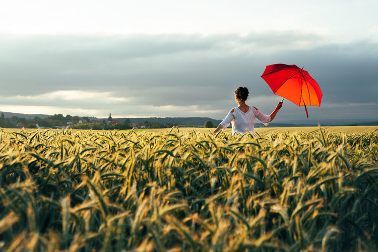 Woman standing  with a red umbrella on field against sky and enjoying the last sunbeams