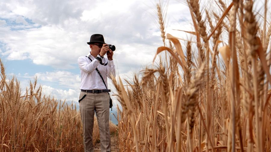 Man photographing with camera while standing amidst crops against sky
