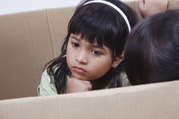 Thoughtful Girl Sitting In Cardboard Box